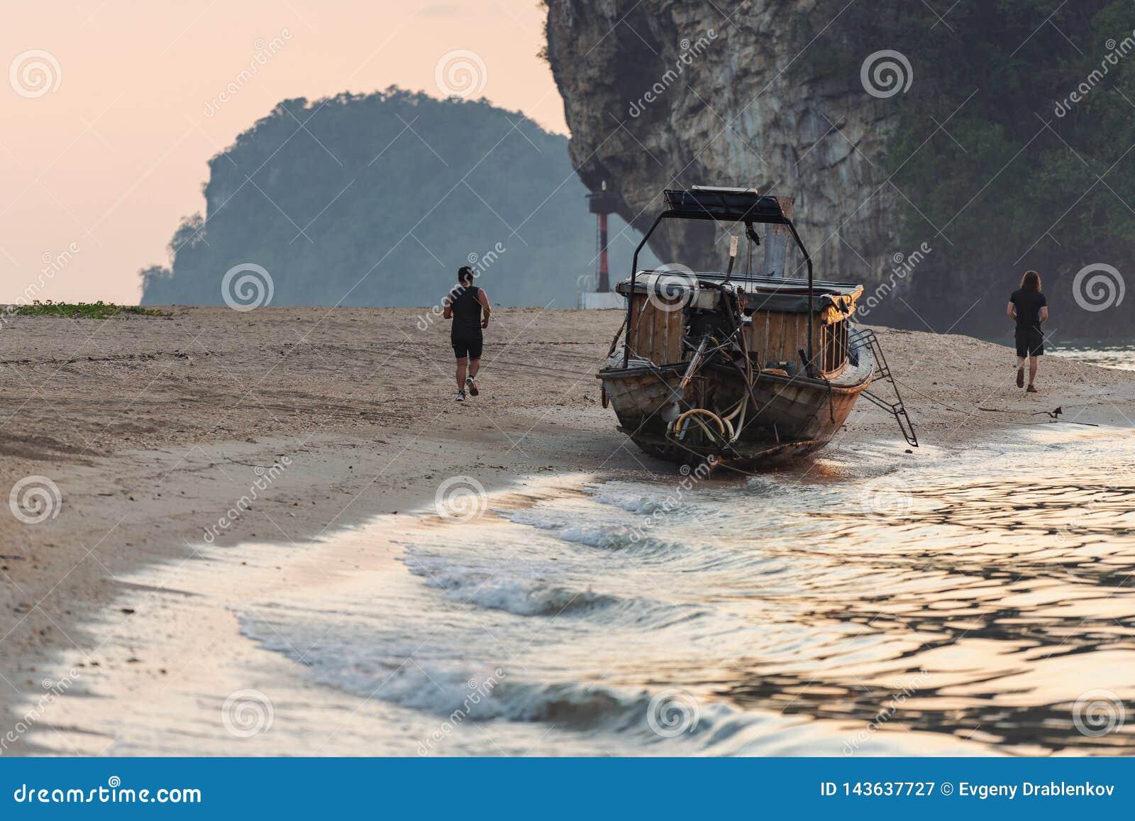 Les gens courant le long du littoral de mer dehors le soir