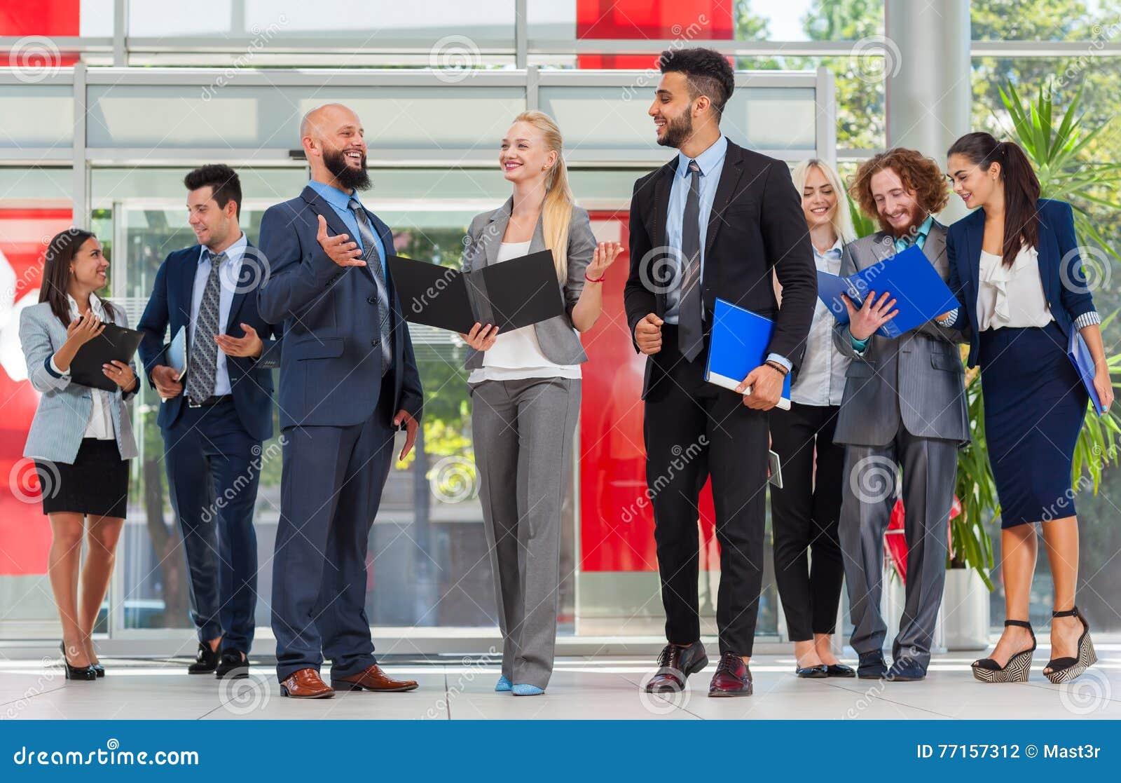 Les gens d affaires groupent discuter le plan de projet de document communiquant, sourire parlant dans le bureau moderne