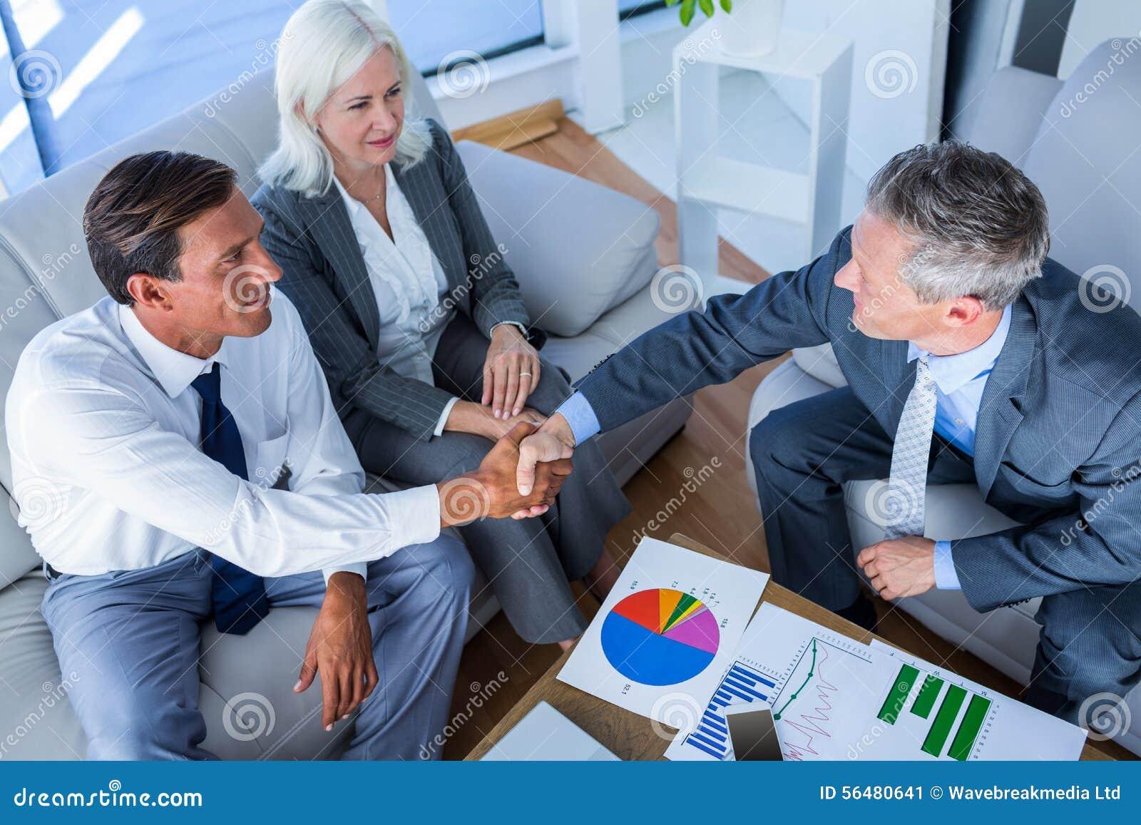 Les gens d affaires se serrent la main sur le divan