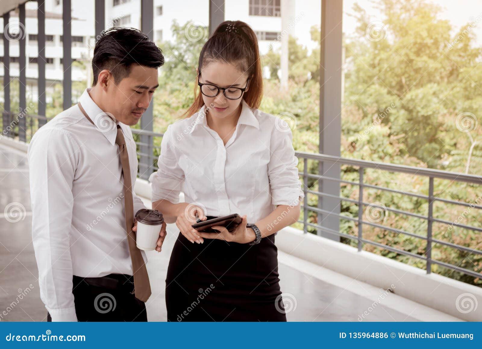 Les gens d affaires travaillant sur le diagramme numérique de comprimé et d analyse rapportent ensemble