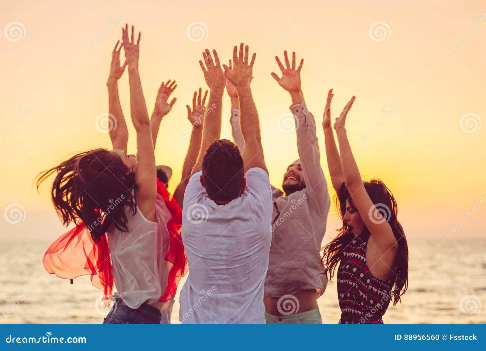 Les gens dansant à la plage avec des mains  concept au sujet de partie, de musique et de personnes
