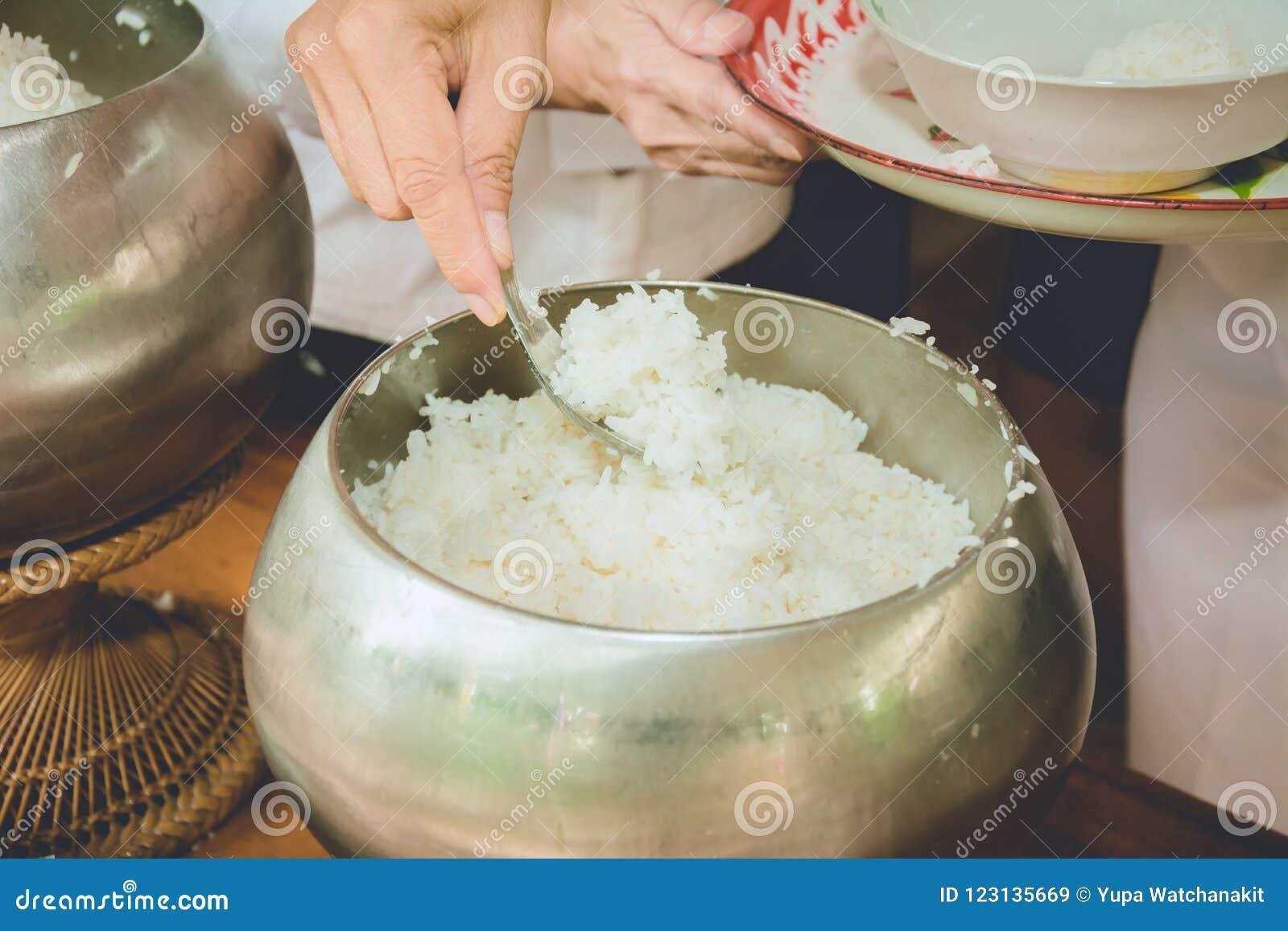 Les gens donnent le riz dans la cuvette d aumône de moine bouddhiste