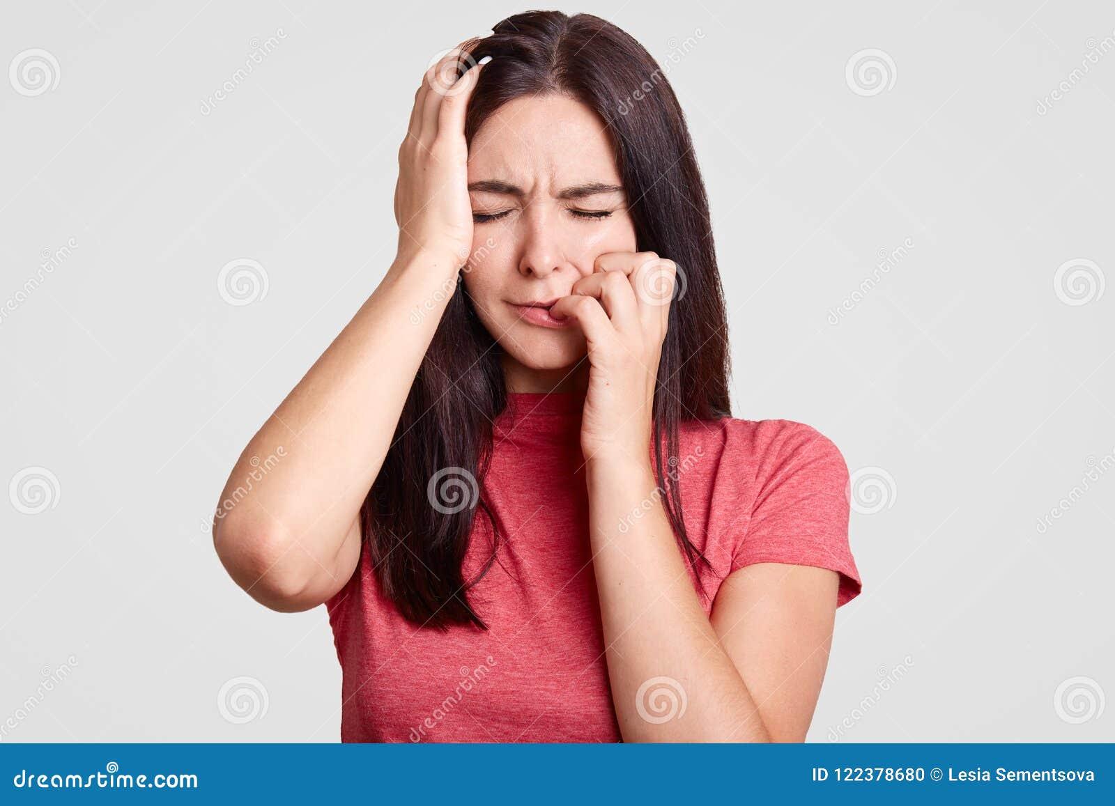 Les gens et le concept de tristesse La femelle soumise à une contrainte de brune maintient des yeux fermés, touche la tête, sent
