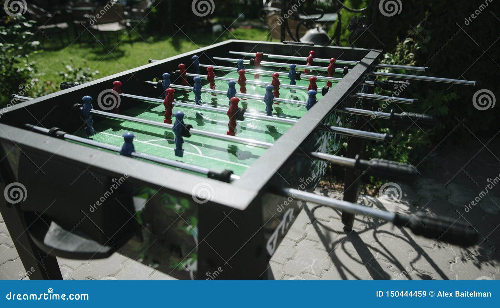 Les gens jouant le plan rapproché du football de table dehors