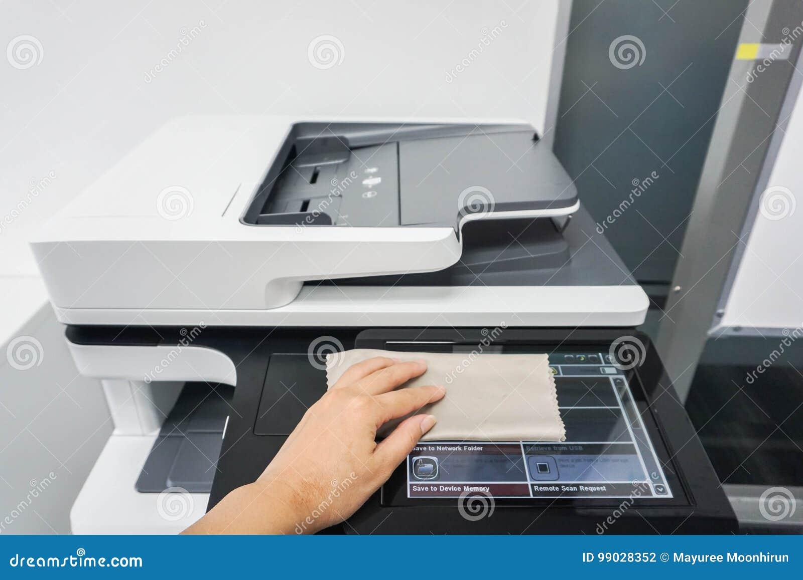 Les gens nettoient l écran tactile de l imprimante de bureau pour