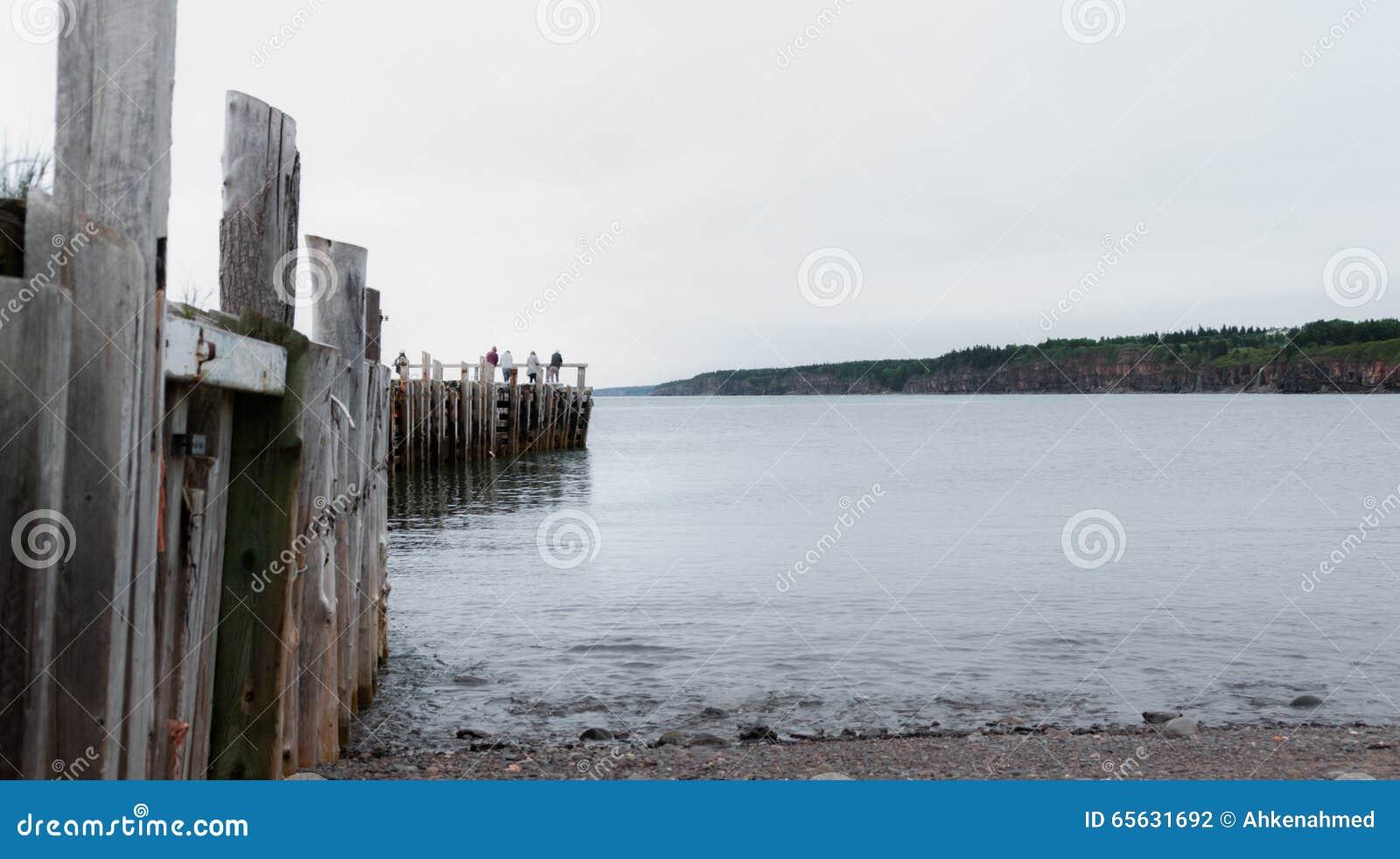 Les gens pêchant à l extrémité d un dock dans le printemps Littoral de Nova Scotia en juin