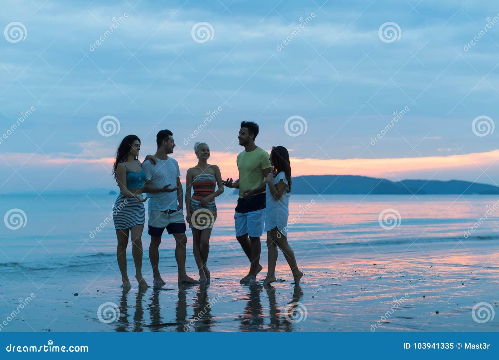 Les gens parlant sur la plage au coucher du soleil, jeune groupe de touristes marchant sur la mer dans la communication de soirée