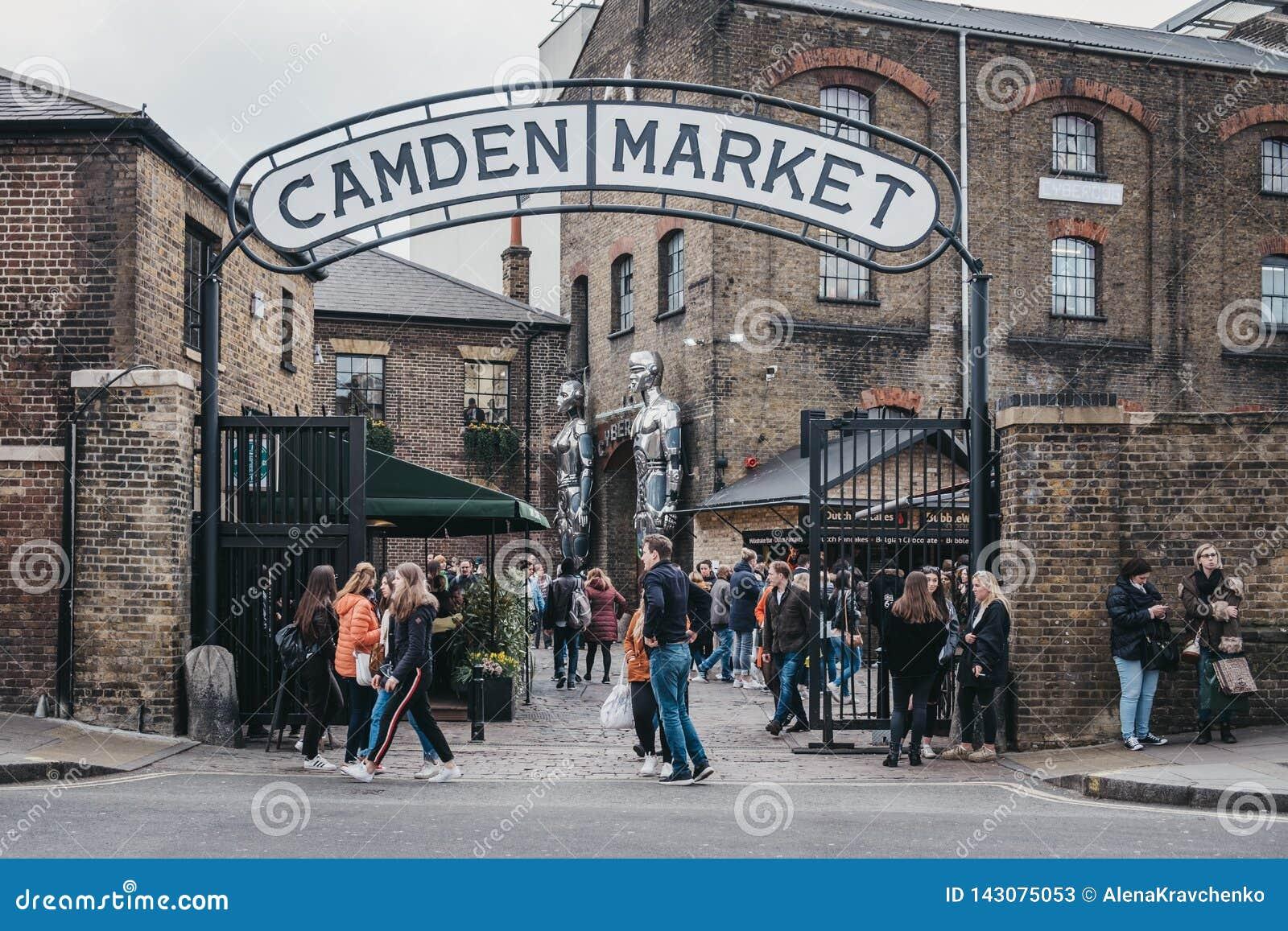 Les gens présentant Camden Market, Londres, R-U, par les portes, sous un signe de nom