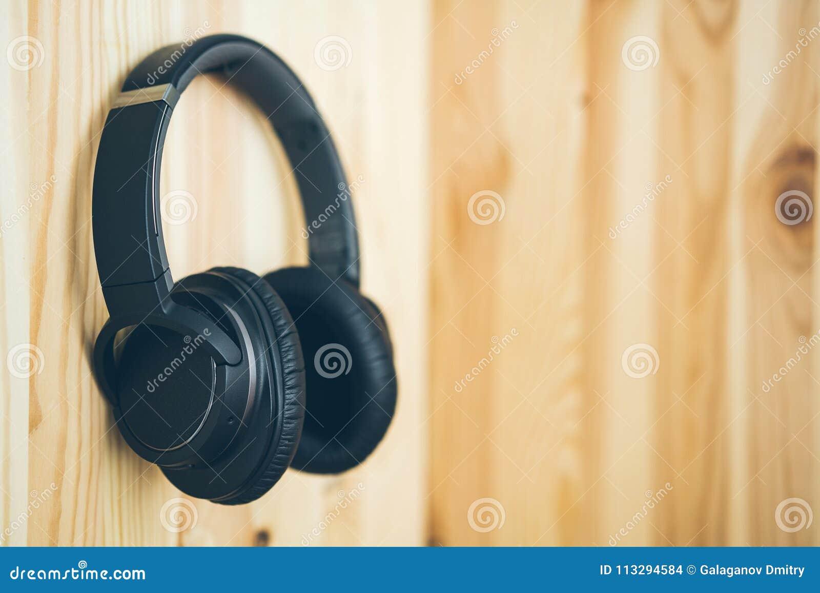 Les grands écouteurs sans fil noirs accrochent sur le clou sur un mur en bois naturel