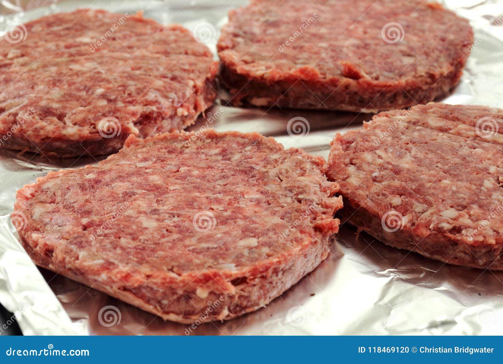 Les hamburgers crus de boeuf sur un aluminium ont couvert le plateau de cuisson