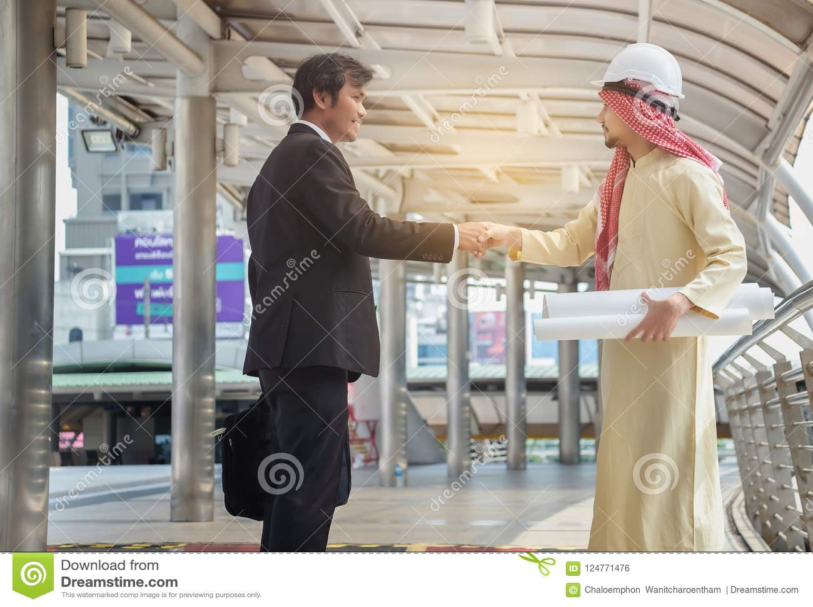Les hommes d affaires asiatiques et les architectes arabes ont la poignée de main convenue sur a