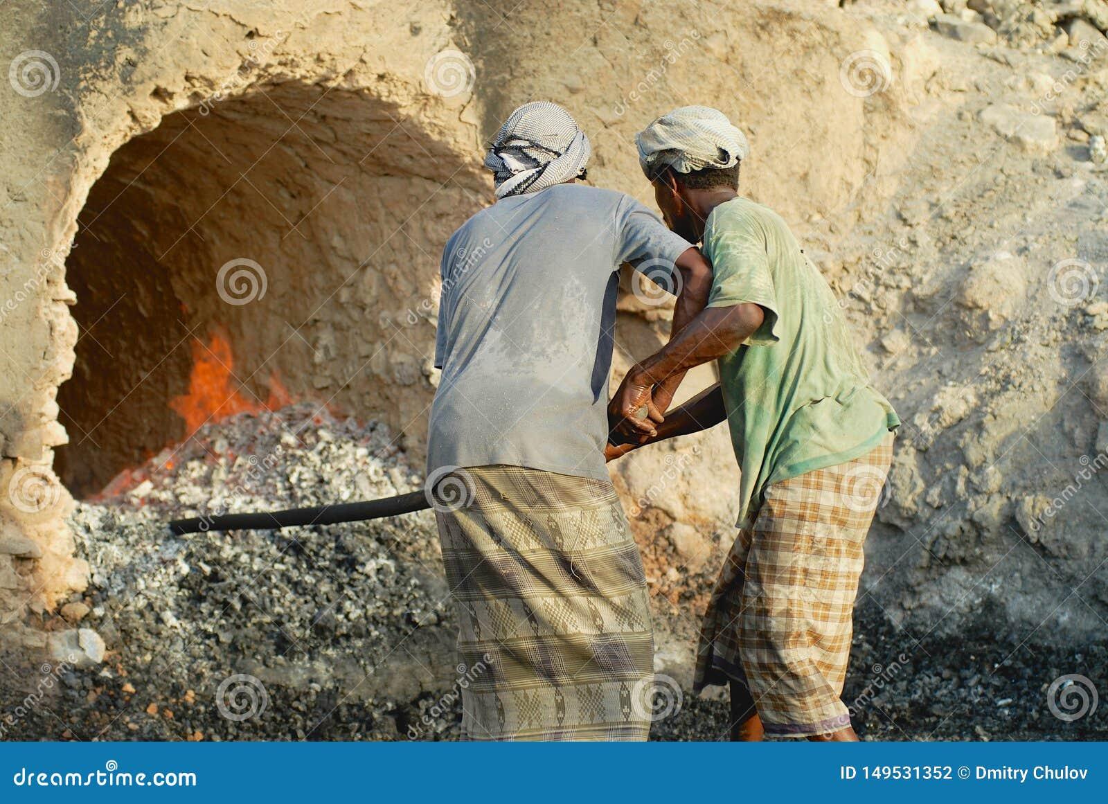Les hommes utilisant les ?charpes principales traditionnelles et injecte le travail ? un four ext?rieur de production de charbon