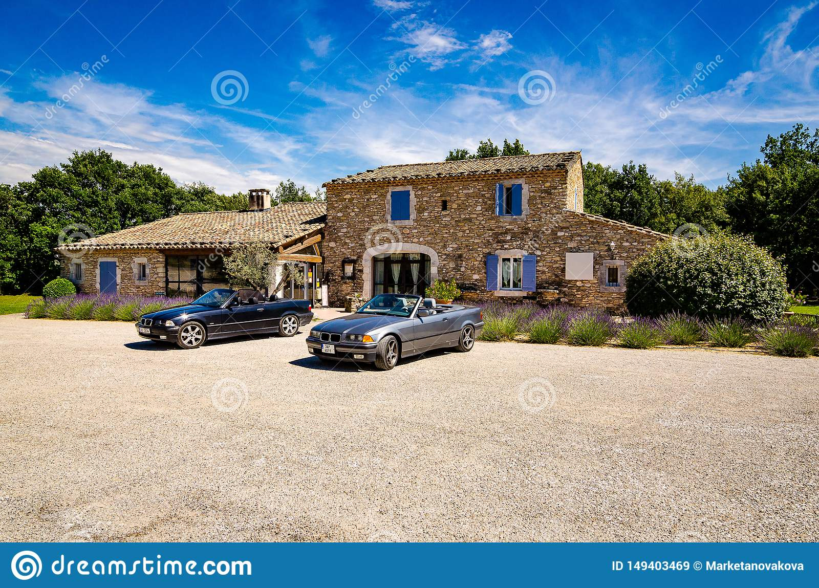 Les Imberts, France - June 16, 2018. Two convertible vintage cars parked in front of typical french provence house