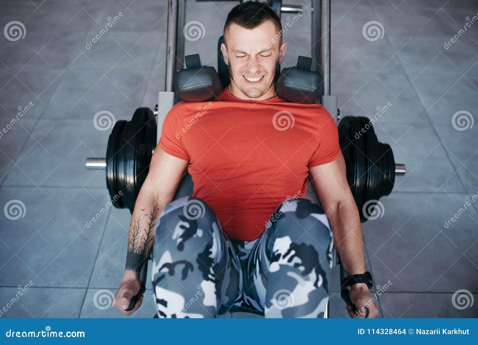 Les jambes convenables de formation d homme sur la jambe pressent la machine dans le gymnase