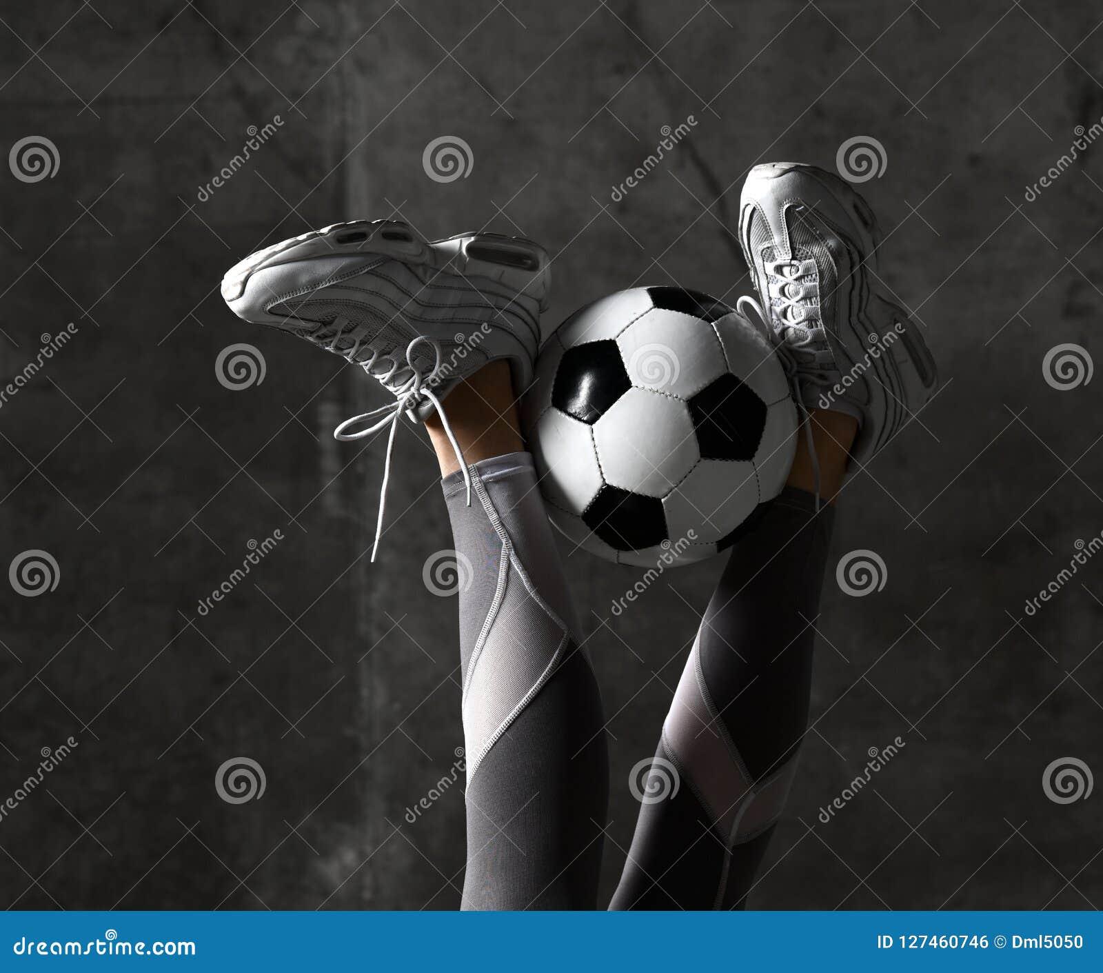 Les jambes de femme avec du ballon de football sur le mur en béton tracent