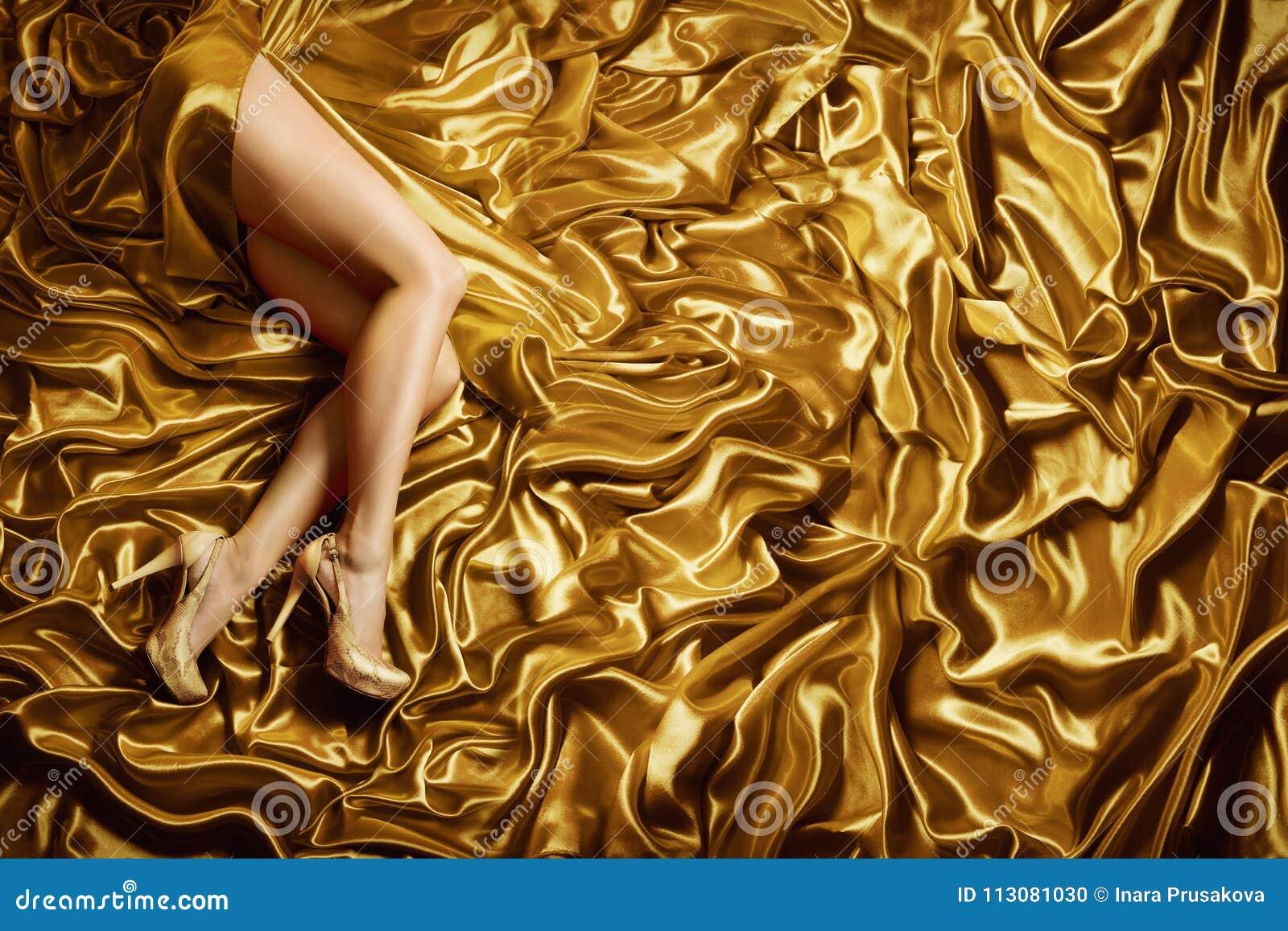 Les jambes de femme sur le fond de tissu en soie d or, façonnent les chaussures d or