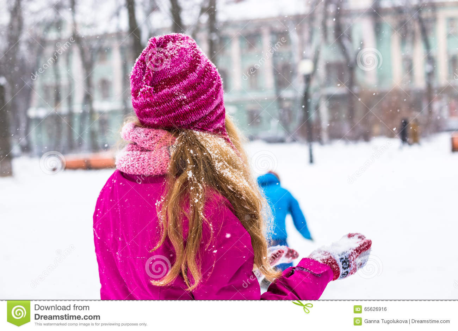 Les jeunes boules de neige womanplay heureuses dans la ville d hiver garent extérieur