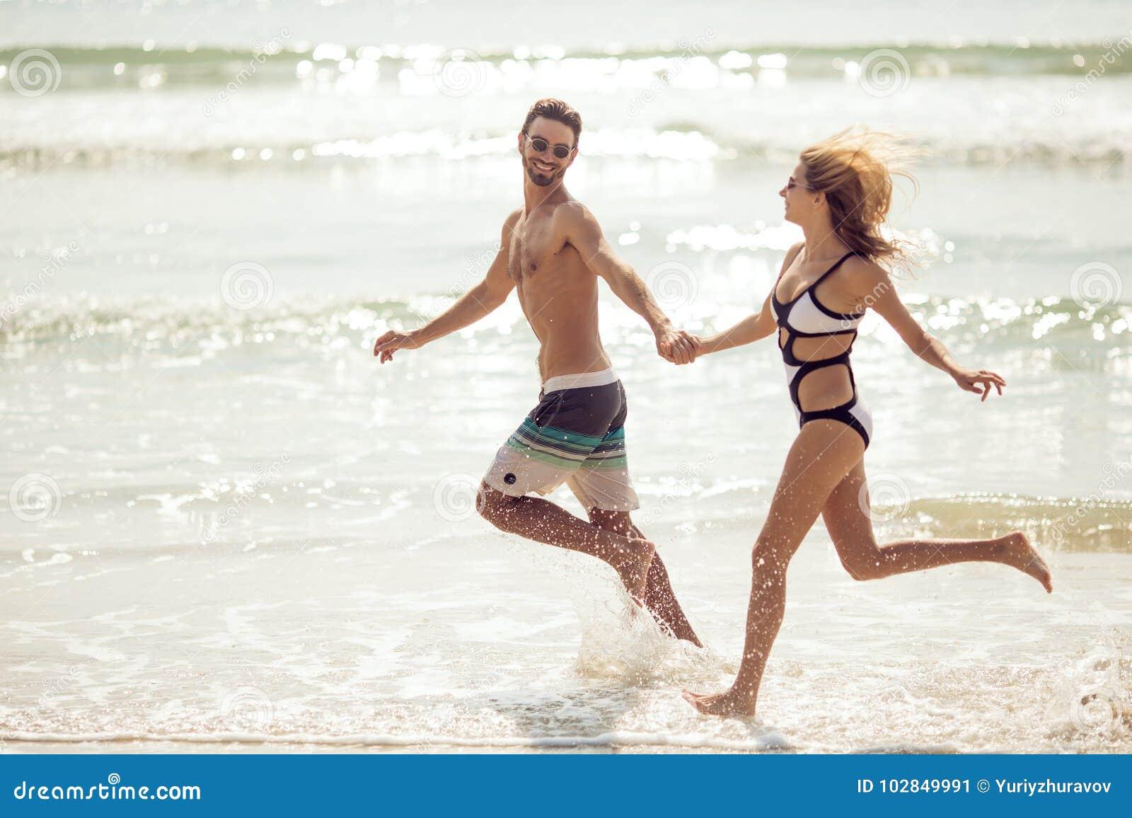 Les jeunes couples attrayants ont l amusement sur la plage