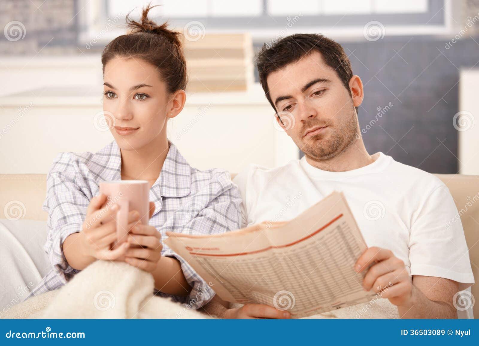 Les jeunes couples dans le lit équipent le thé potable de femme de lecture