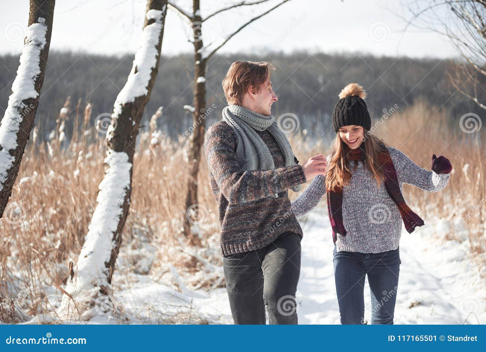Les jeunes couples heureux en hiver stationnent avoir l amusement Famille à l extérieur