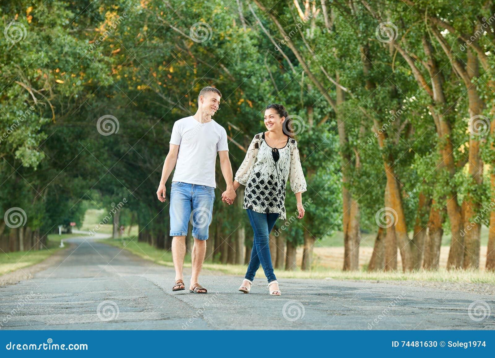 Les jeunes couples heureux marchent sur la route de campagne extérieure, concept romantique de personnes, saison d été