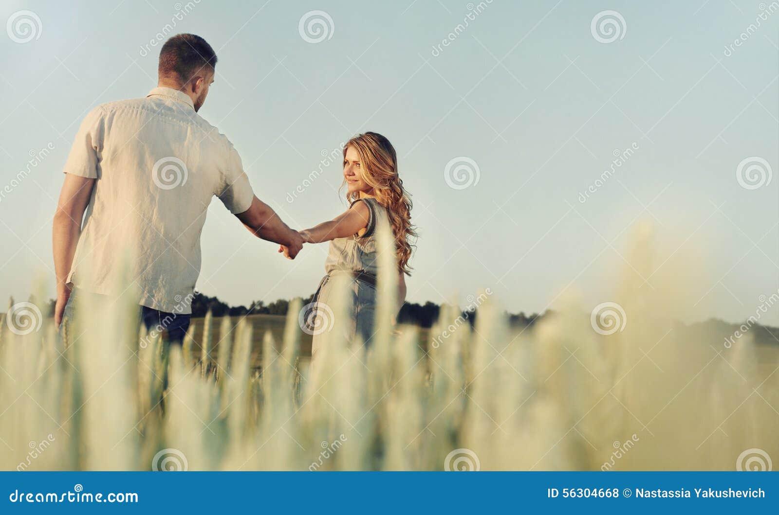 Les jeunes couples heureux renversants dans l amour posant en été mettent en place le holdi