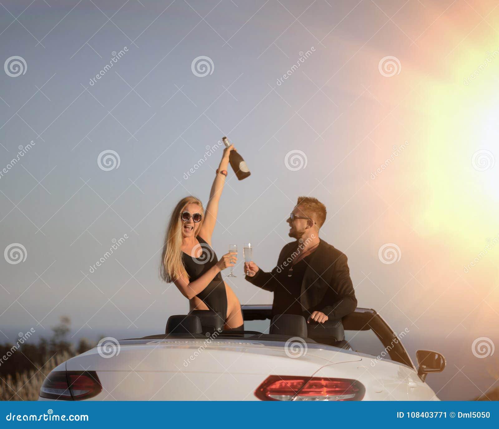 Les jeunes couples ont le champagne potable de fête de vacances aux acclamations de plage