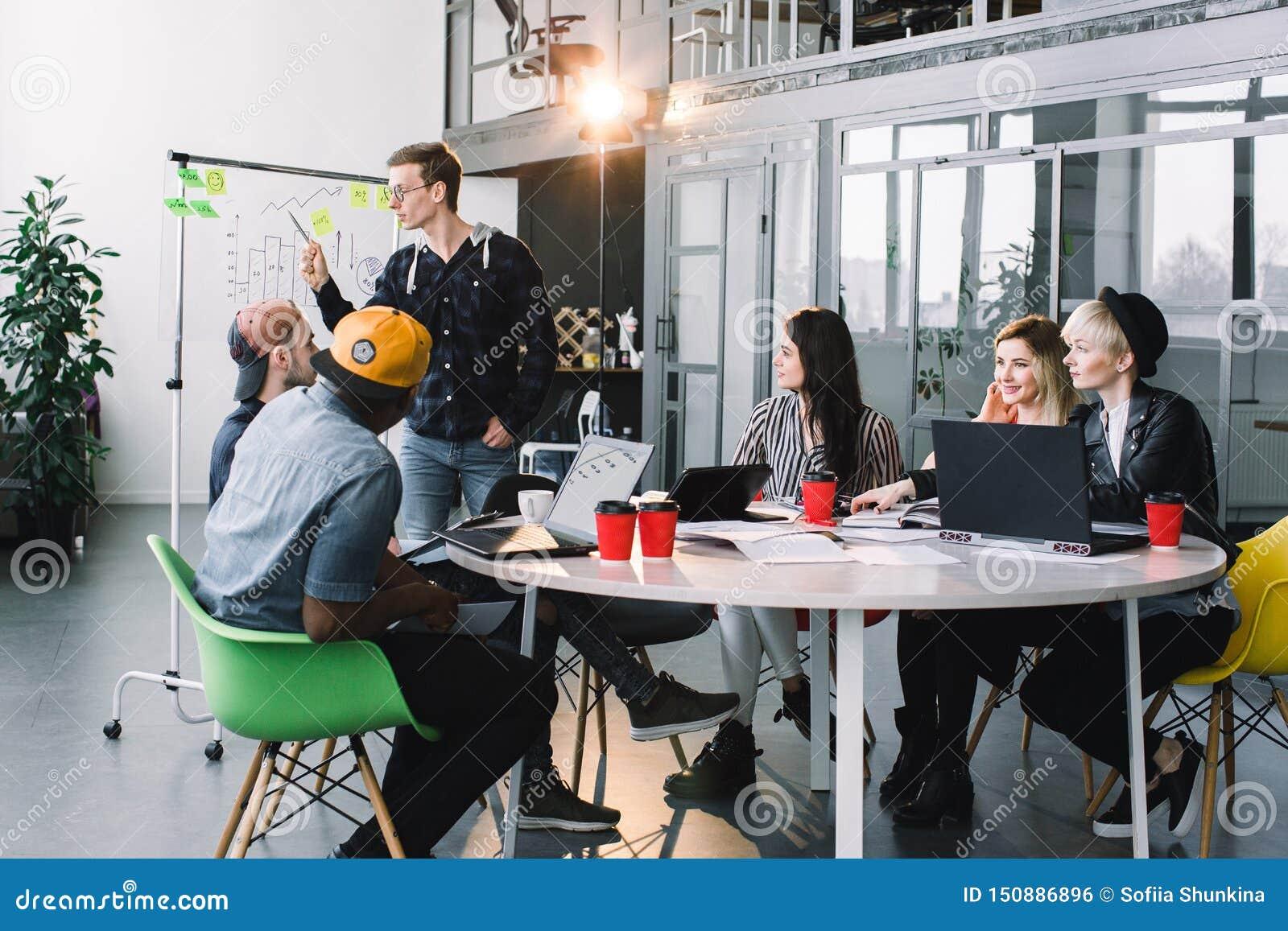 Les jeunes créatifs multiraciaux dans le bureau moderne collaborent avec l ordinateur portable, comprimé, téléphone intelligent,