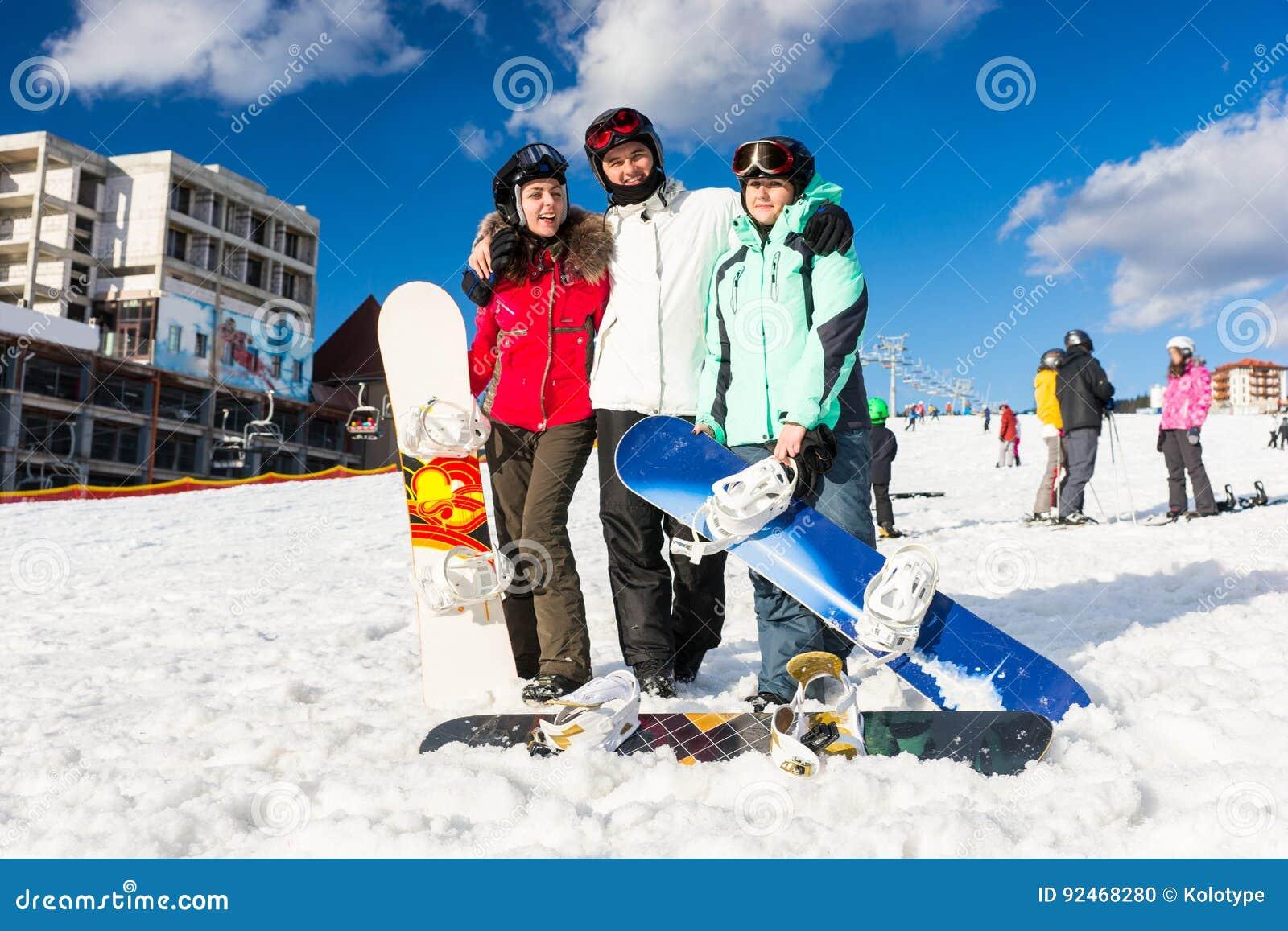 75946354d9 Les jeunes dans les ski-costumes et les lunettes de ski ayant l amusement  tandis