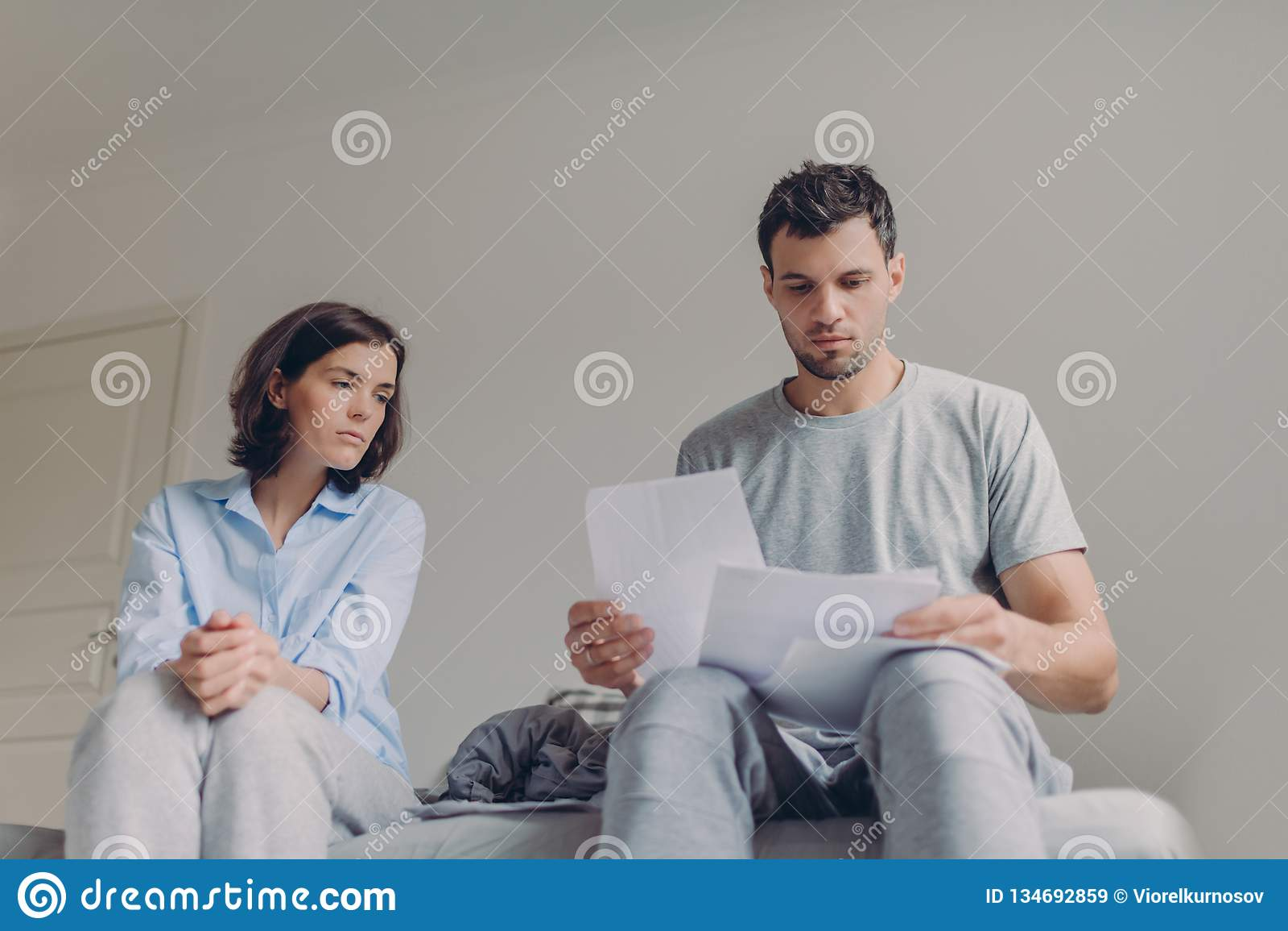 Les jeunes documents sérieux d étude de couples ensemble au lit, ont des regards sérieux, plan leur budget, pose contre l intérie