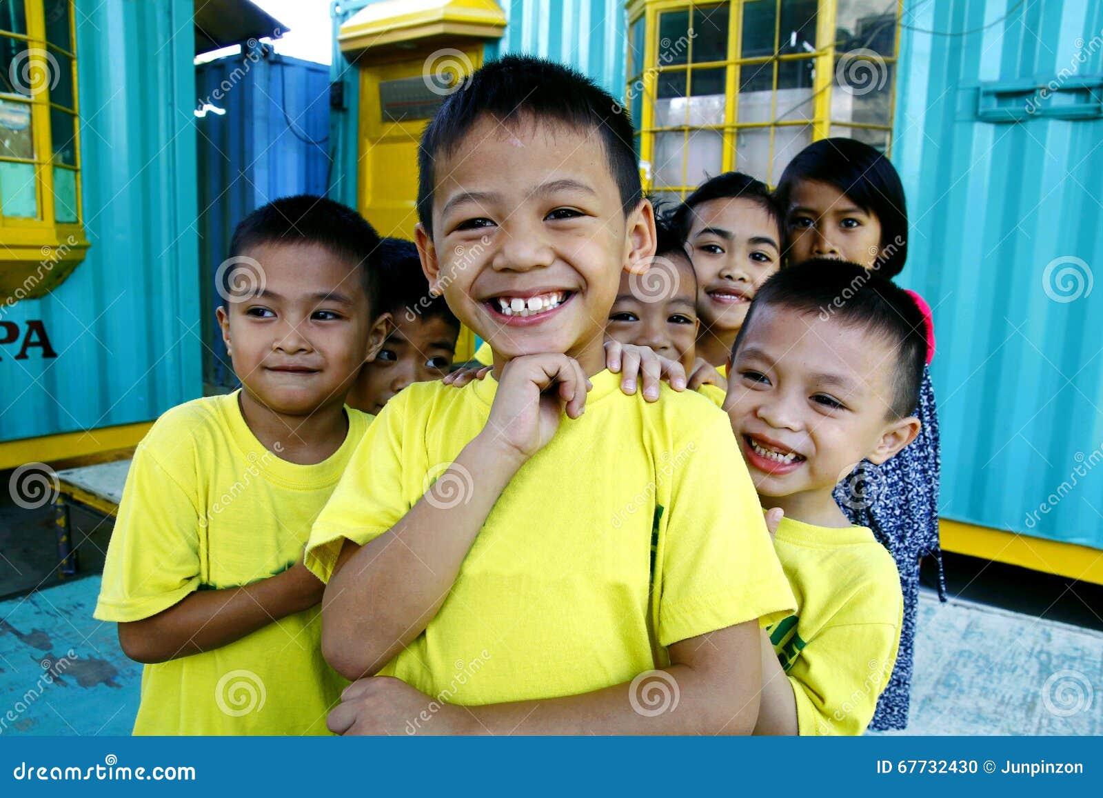 Les jeunes garçons et filles se blottissent et sourient pour l appareil-photo