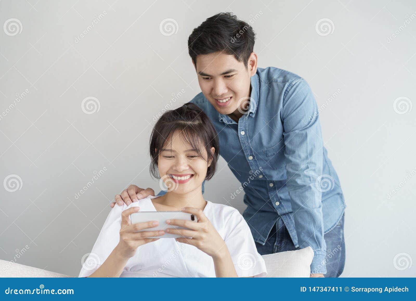 Les jeunes heureux aiment les couples asiatiques se reposant sur le divan ? la maison, regardant le t?l?phone portable, les jeune