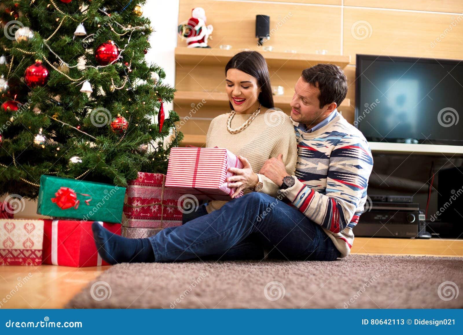Les jeunes heureux donnent des cadeaux par l arbre de Noël