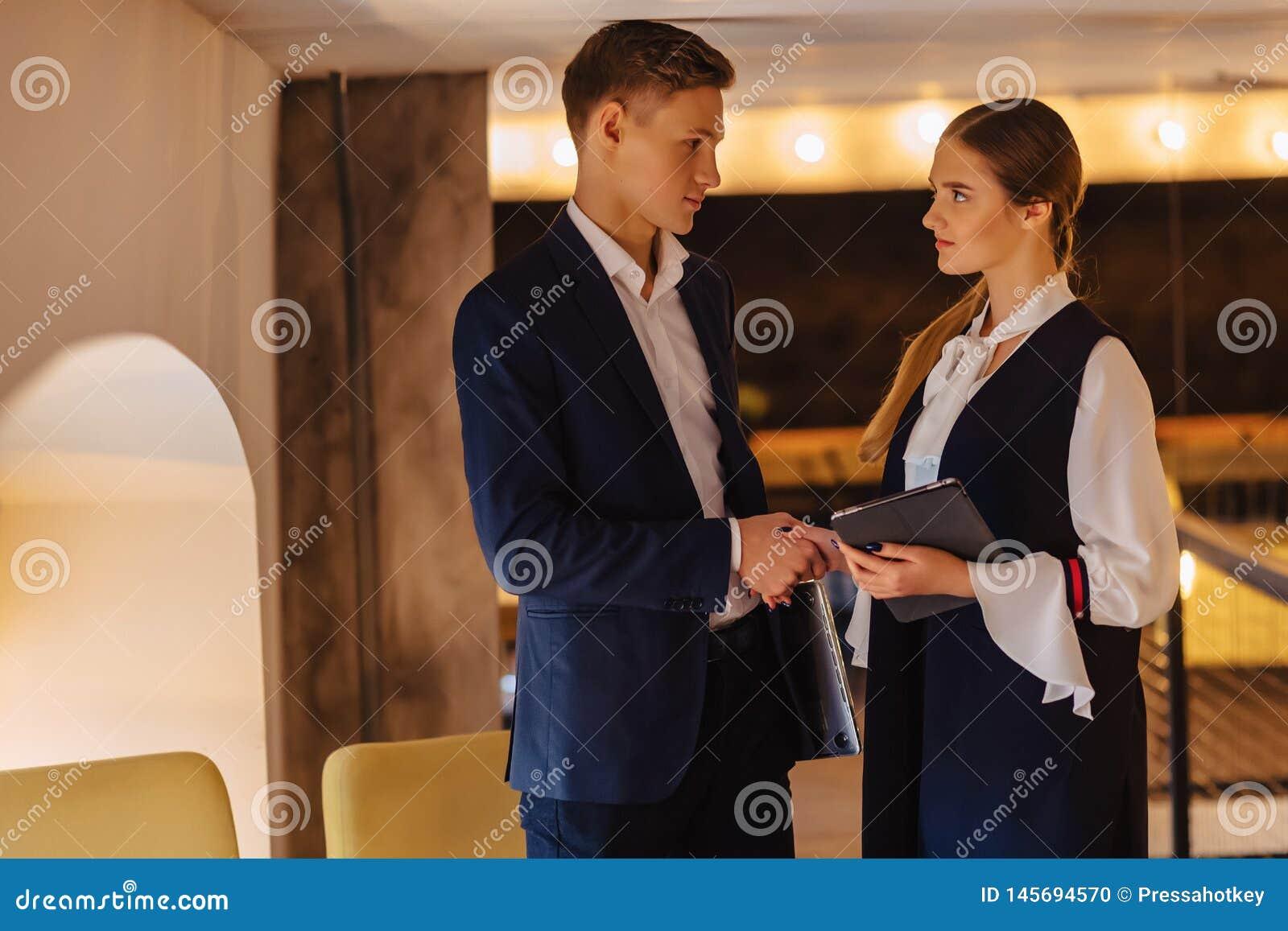 Les jeunes hommes d affaires type et fille dans un int?rieur confortable ont convenu, des affaires et ind?pendant