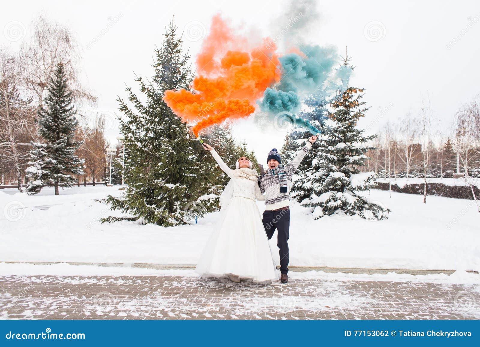 Les jeunes mariés avec des bombes fumigènes en hiver