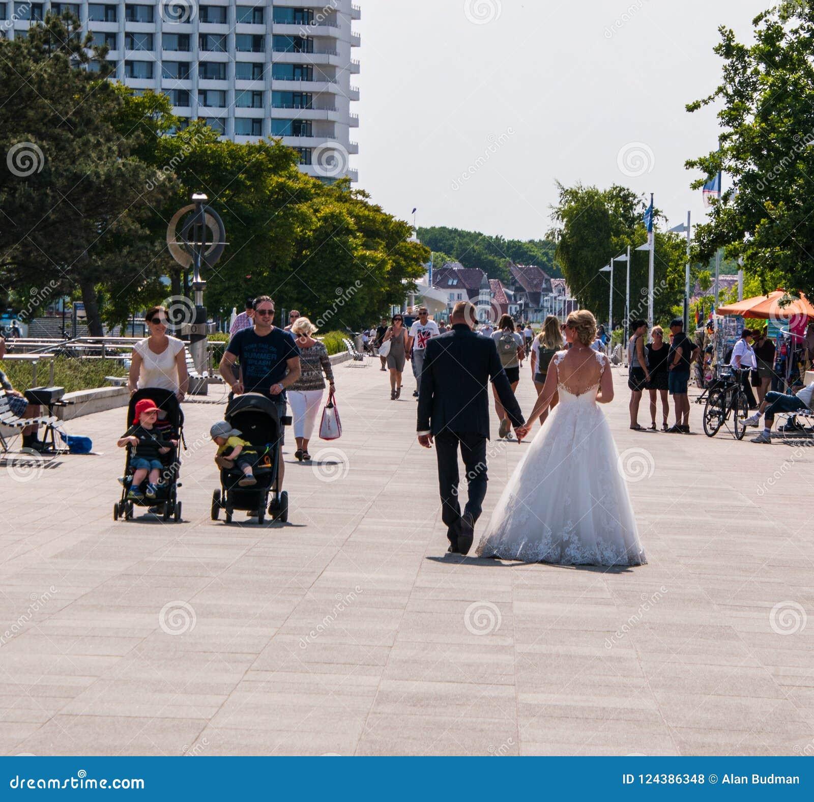 Les jeunes mariés dans la robe de mariage et le smoking marchent après un ajouter à deux enfants dans des poussettes sur le trott