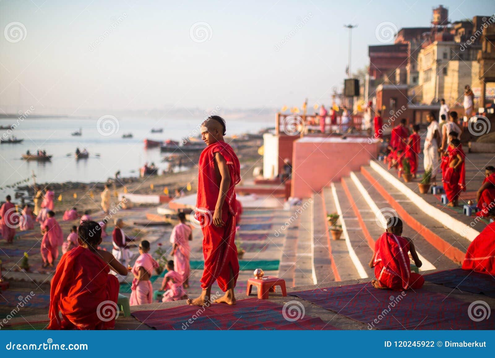 Les jeunes moines indous conduisent une cérémonie pour rencontrer l aube sur les banques du Gange, et soulèvent le drapeau indien