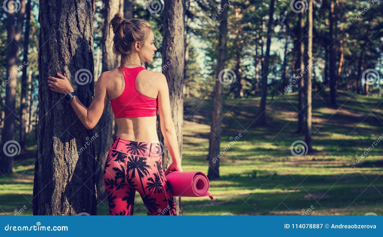 Les jeunes ont adapté la femme sportive dans une forêt utilisant la montre intelligente et tenant le tapis de yoga Esprit et conc