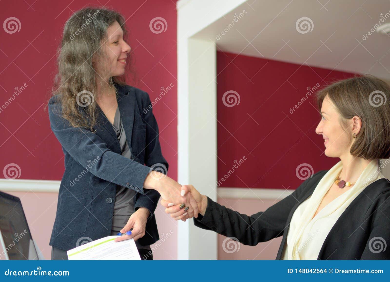 Les jeunes ont vivement habill? la dame aident une autre jeune dame ? travailler avec des documents, des formes de suffisance et