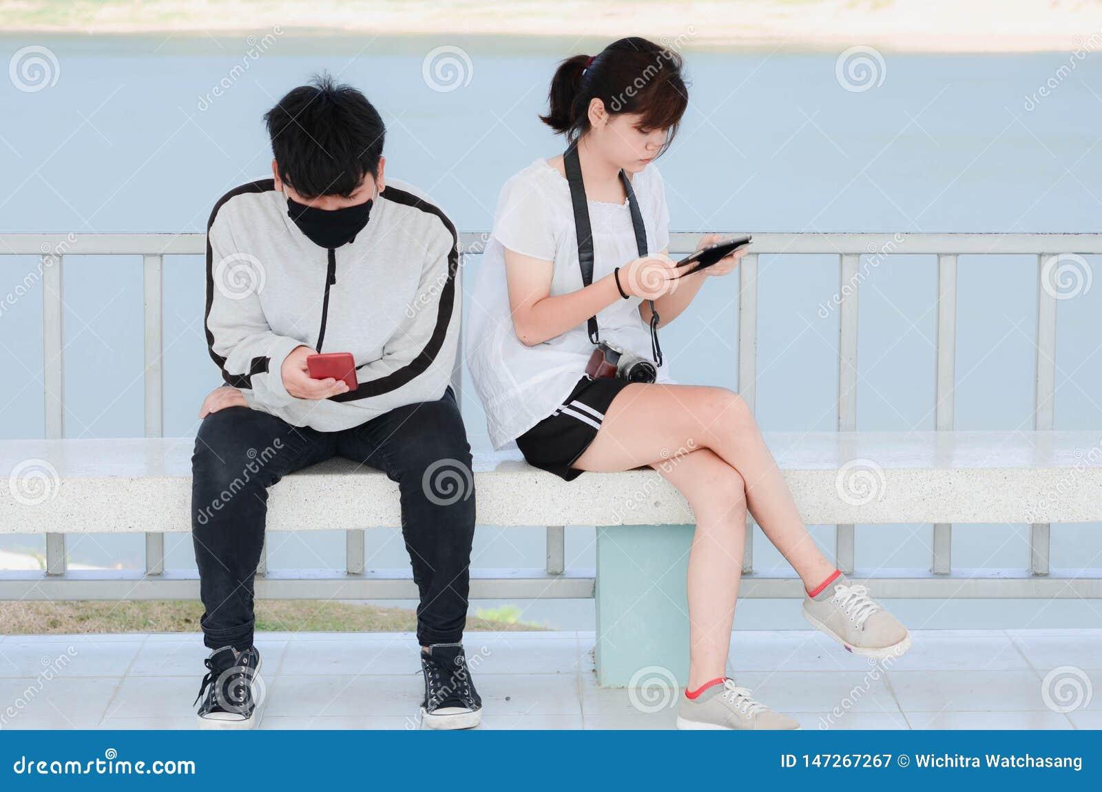 Les jeunes sérieux utilisant des smartphones se reposant en parc