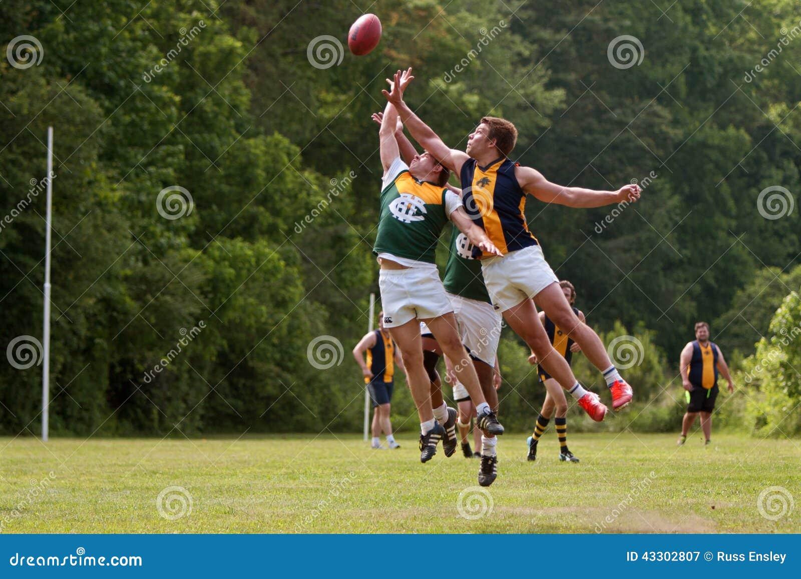 Les joueurs sautent pour la boule en partie de football de règles d Australien