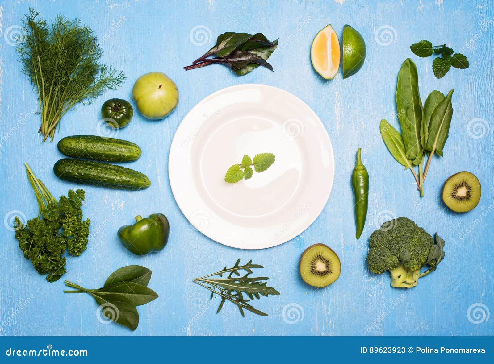 les légumes verts portent des fruits et des herbes autour du plat