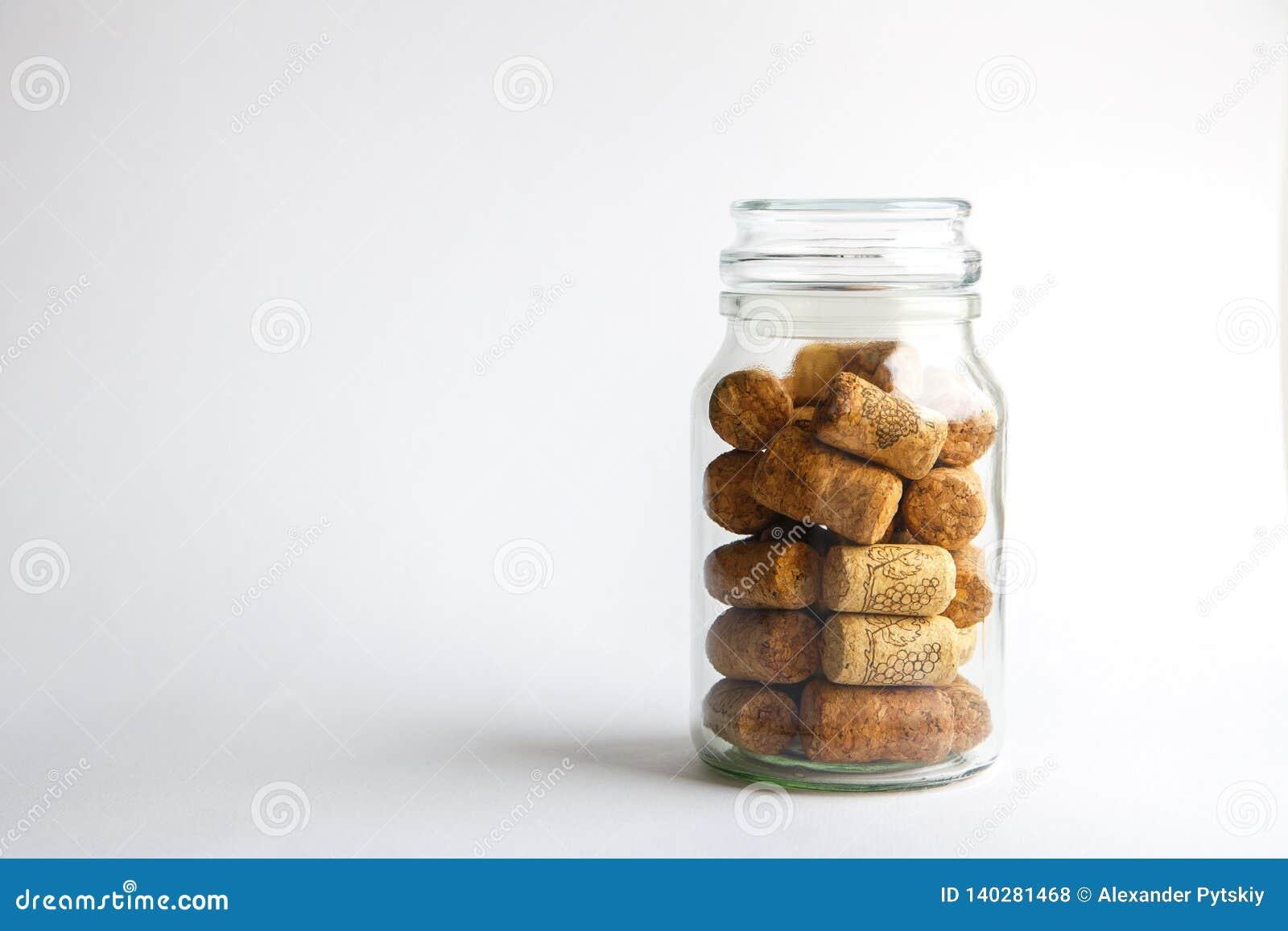 Les lièges de vin se situent dans un pot en verre sur un fond blanc