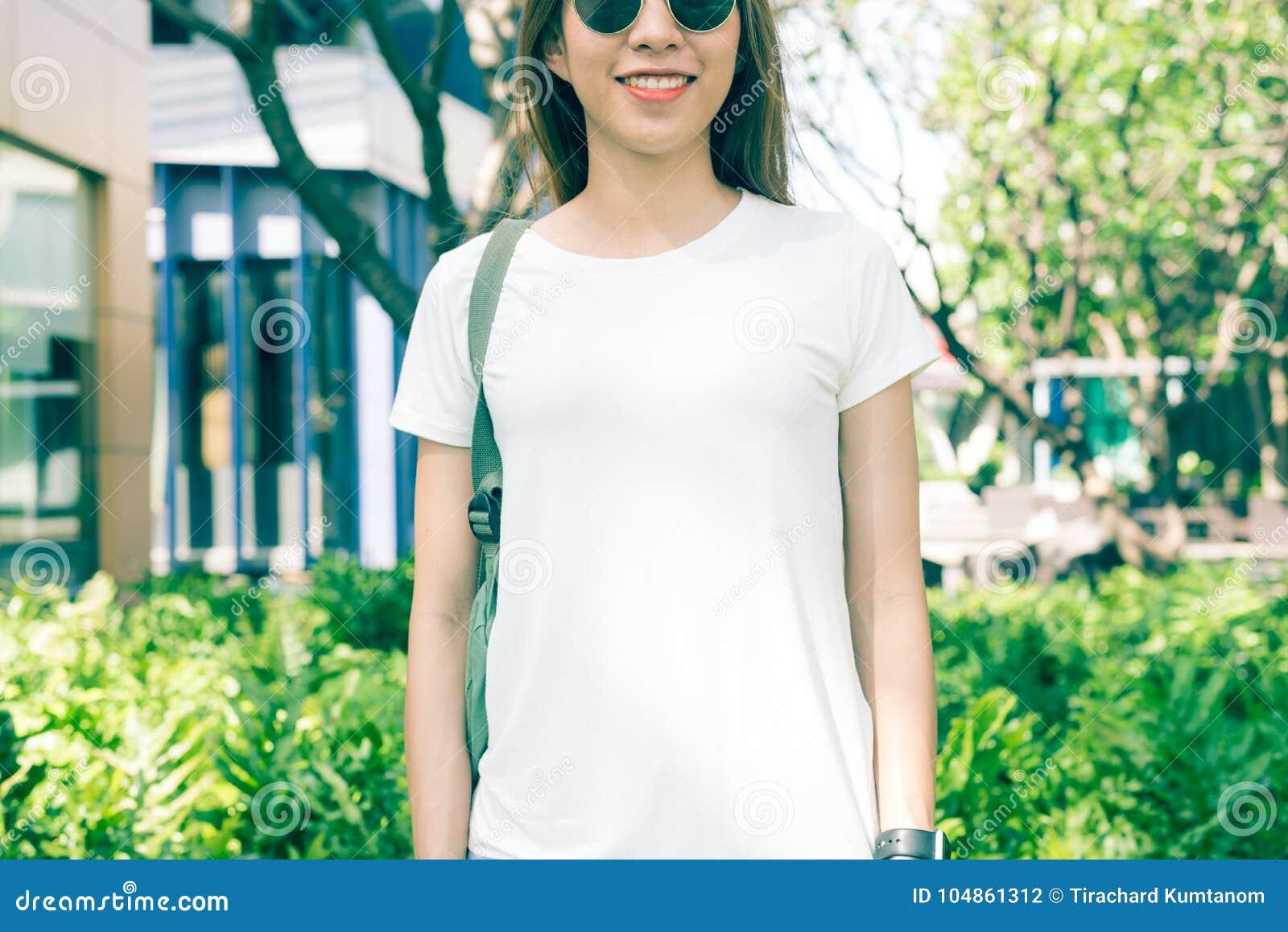 Les longs cheveux bruns de fille asiatique de hippie dans le T-shirt vide blanc se tiennent au milieu de la rue
