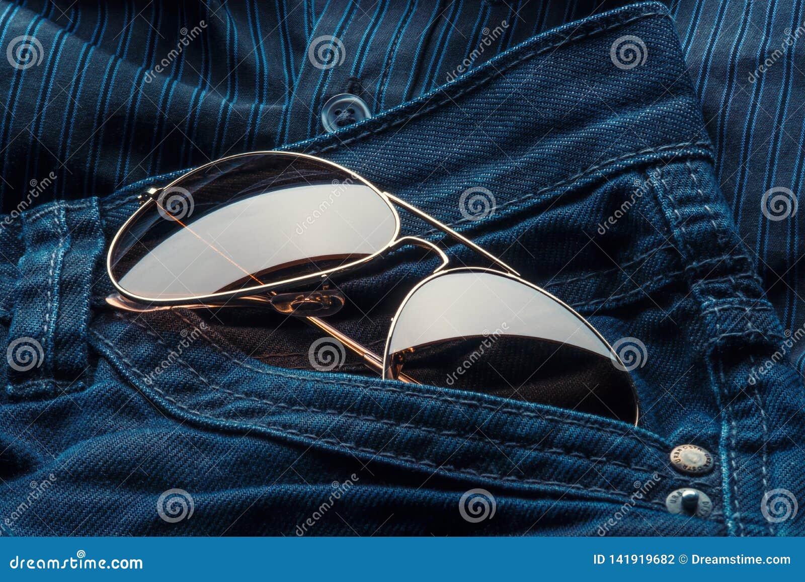 Les lunettes de soleil d aviateur dans des jeans empochent
