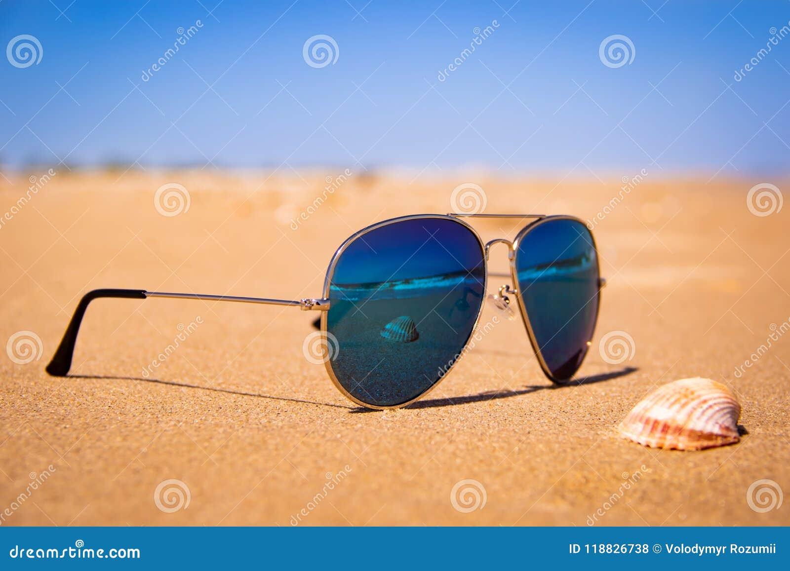 Les lunettes de soleil de miroir sur la plage, la coquille et la mer orageuse sont reflétées dans les verres