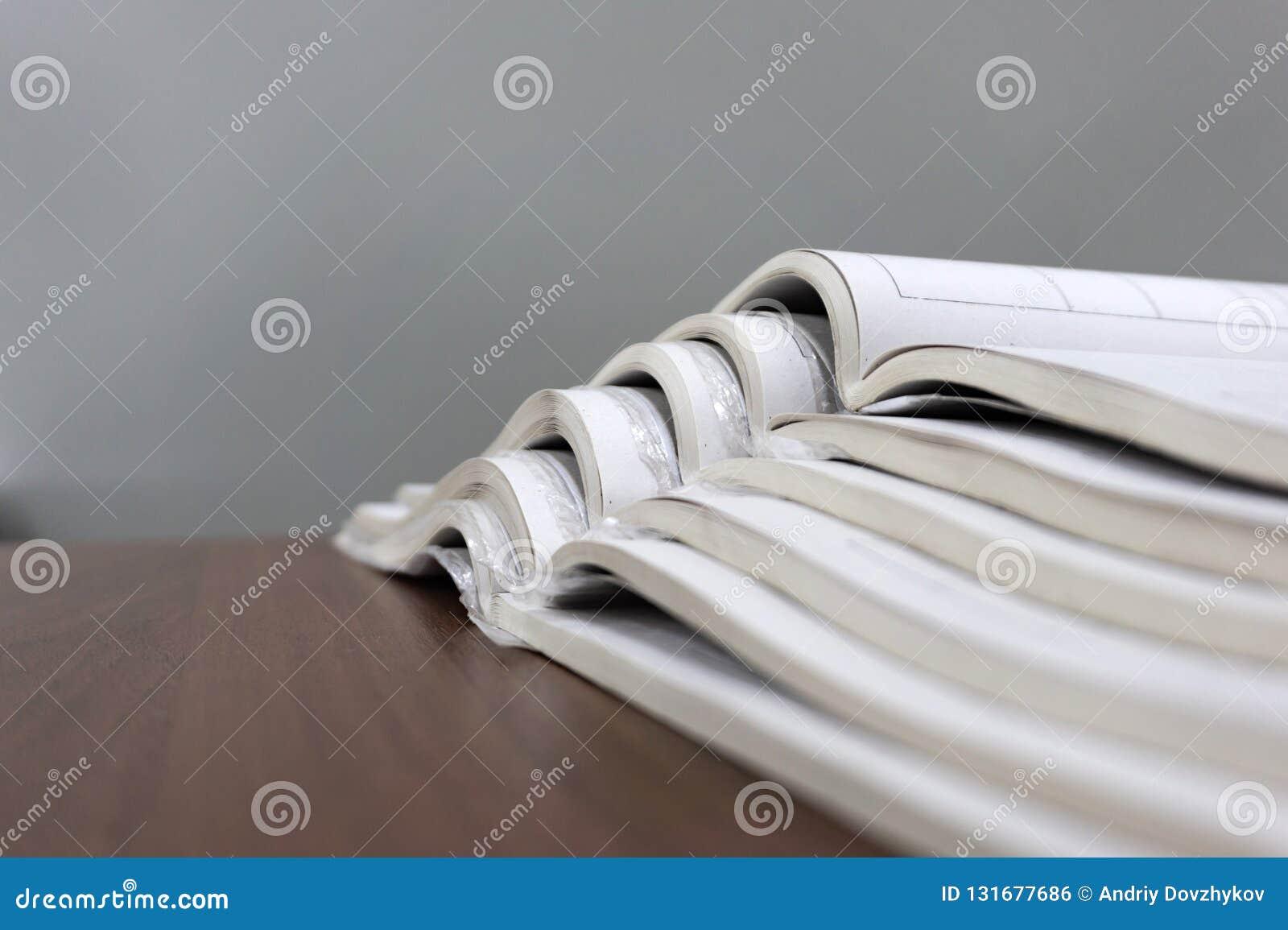 Les magazines ouvertes se trouvent sur l un l autre sur une table brune, documents sont en gros plan empilé