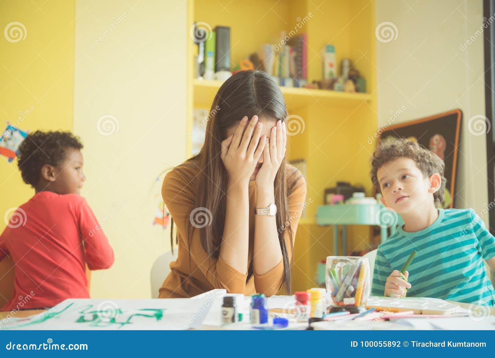 Les mains asiatiques de jardin d enfants de professeur ont fermé les deux oreilles de elle dans un renversement de pour apaiser v