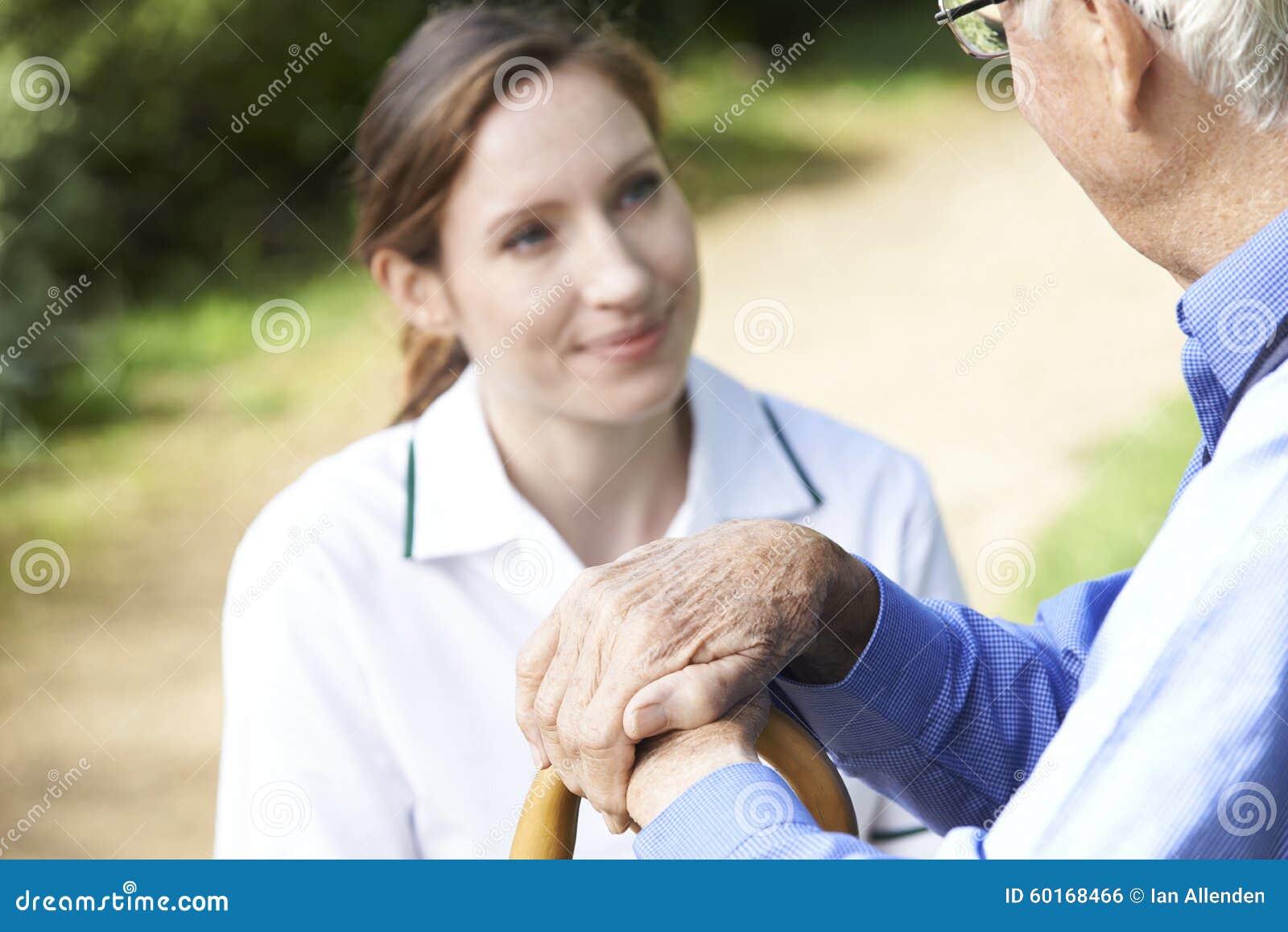Les mains d homme supérieur se reposant sur le bâton de marche avec le travailleur de soin dedans