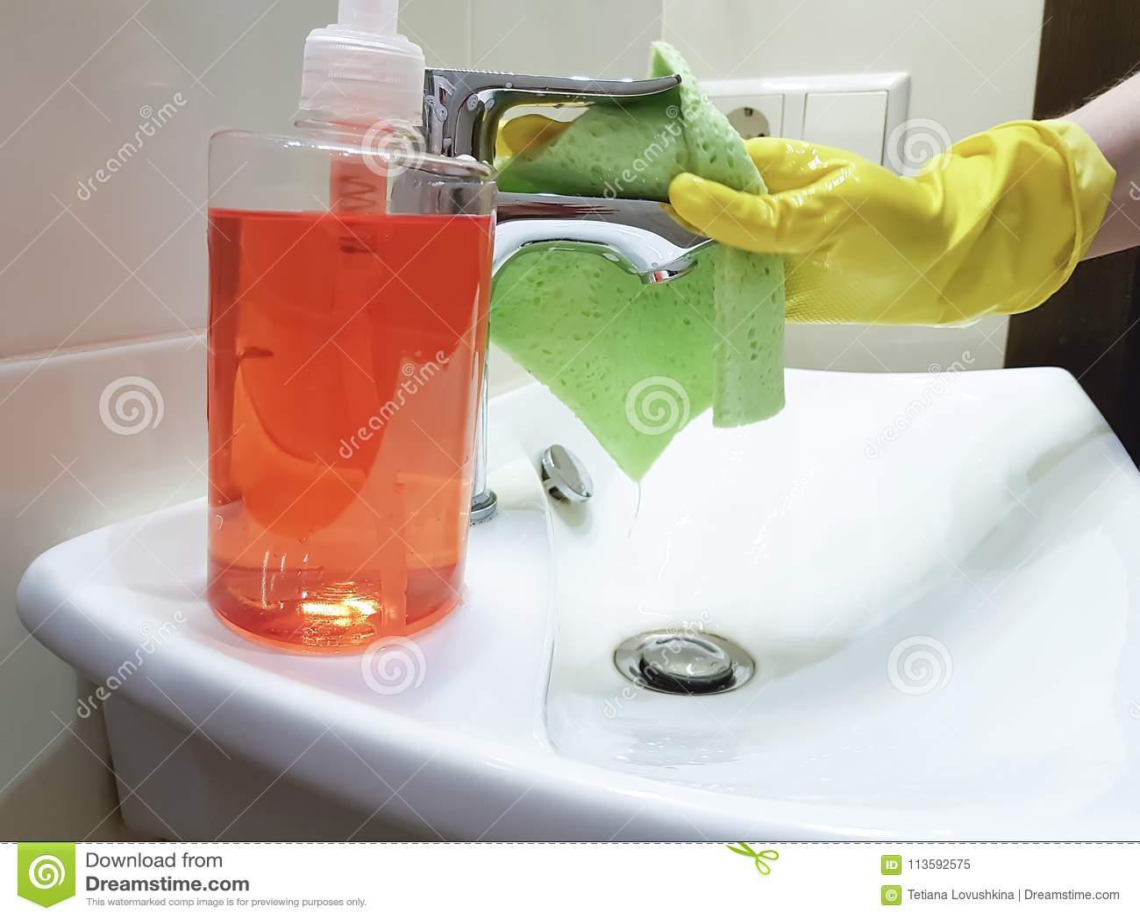 Les mains dans les gants jaunes lavent le ménage de ménage d évier